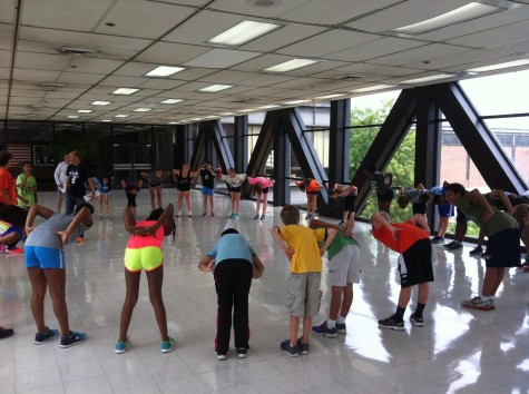 Members of the Academic Center Cross Country team stretch during a summer practice